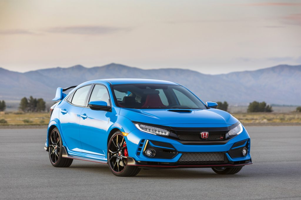A blue 2020 Honda Civic Type R parked on display with a mountain range in the background