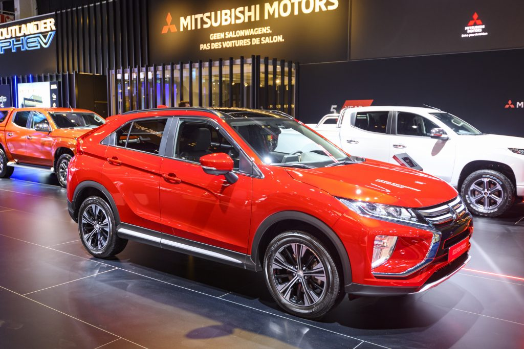 A red 2020 Mitsubishi Eclipse Cross on display at an auto show with some other SUVs in the background