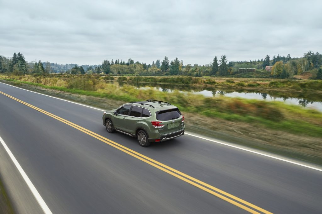 A green 2020 Subaru Forester compact crossover SUV travels on a two-lane highway past foliage and a canal