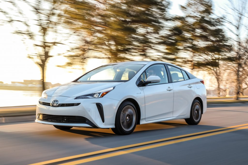 A white 2020 Toyota Prius, a Consumer Reports Green Choice, travels on a two-lane highway lined with trees and a body of water