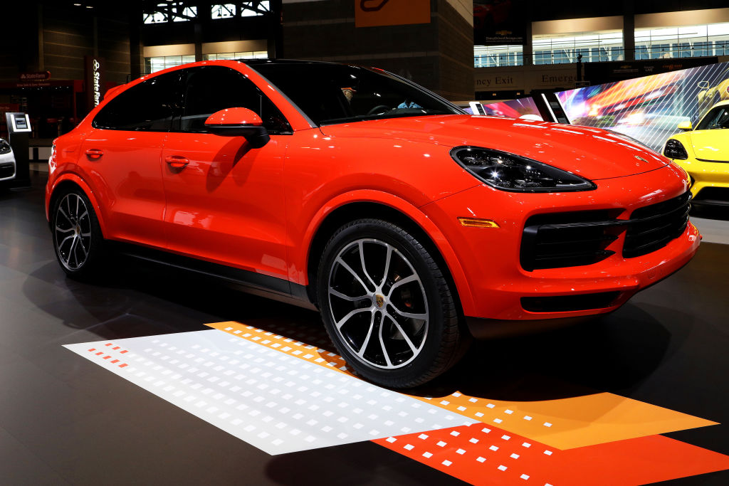 A vibrant red 2020 Porsche Cayenne Coupe on display at an indoor show