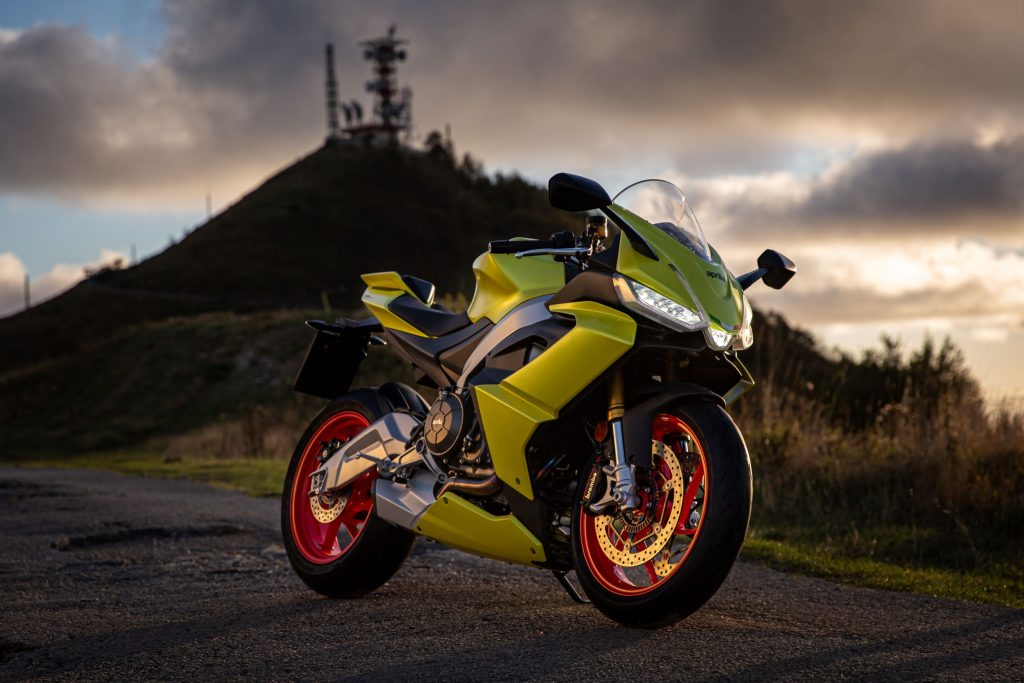 A highlighter-yellow 2021 Aprilia RS 660 parked by a hill at sunset