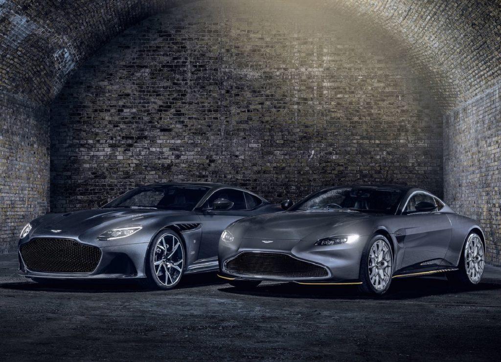 A gray 2021 Aston Martin Vantage 007 Edition and DBS Superleggera 007 Edition by a cobblestone wall