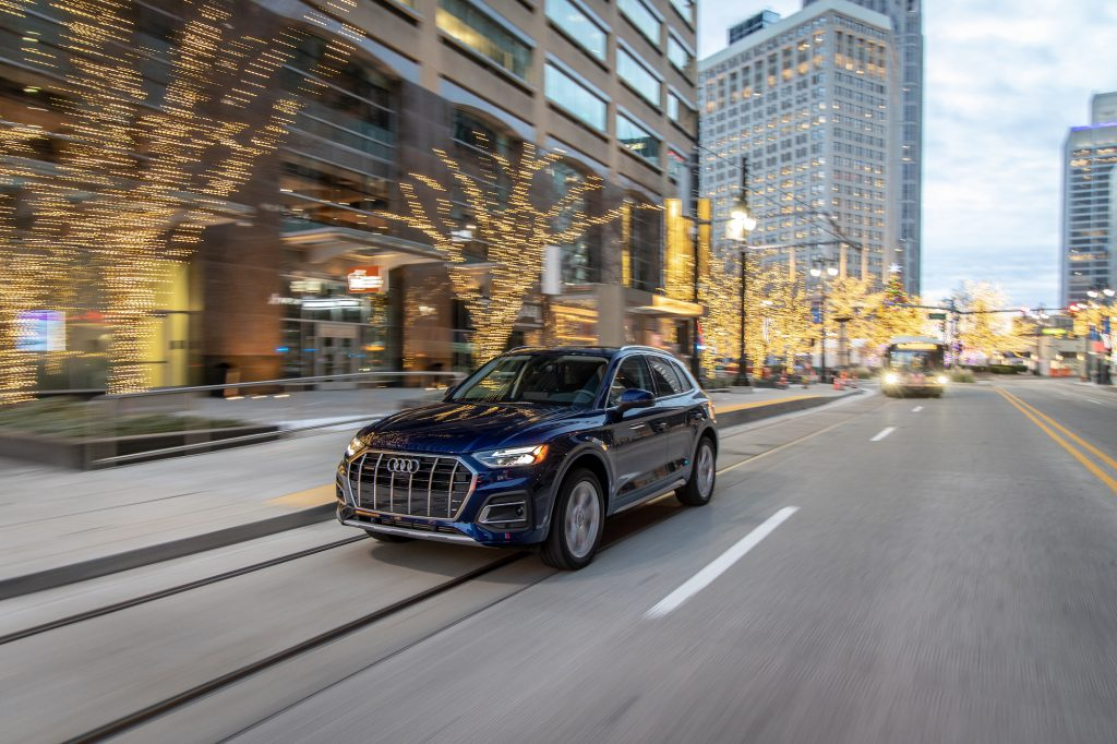 A dark-blue 2021 Audi Q5 compact luxury SUV travels on a city street lined with office buildings and leafless trees strung with glowing twinkle lights at dusk