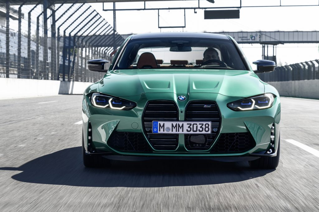 Front view of a green 2021 BMW M3 sports sedan traveling on a racetrack's straightaway