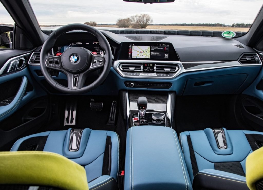 The blue-leather-trimmed carbon-fiber front seats and black carbon-fiber-trimmed dashboard of the 2021 BMW M4 Competition