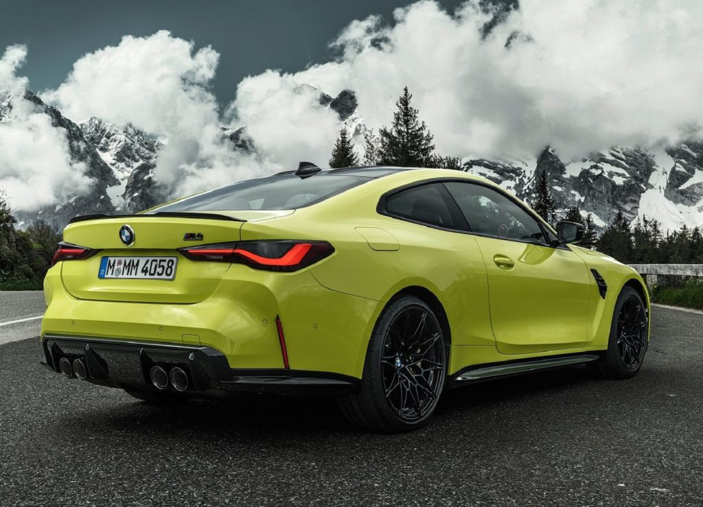 The rear 3/4 view of a bright-green 2021 BMW M4 Competition on a forested mountain road