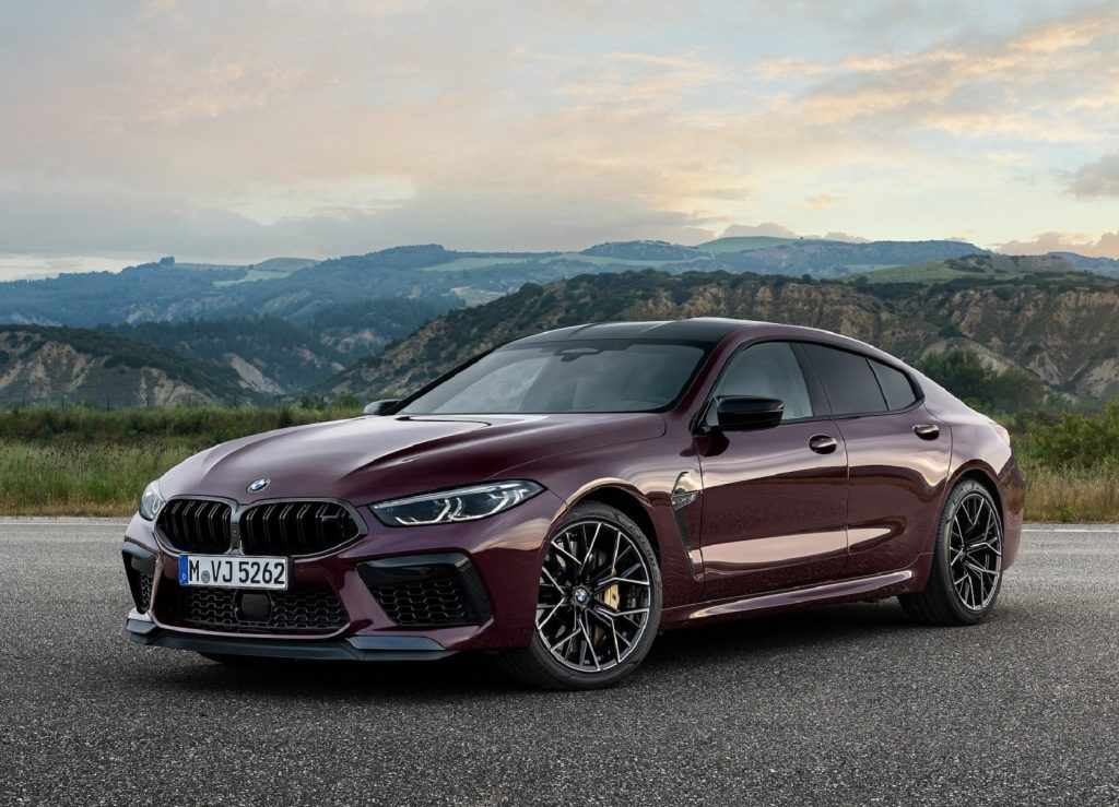 A dark-purple 2021 BMW M8 Competition Gran Coupe parked on a mountain-side overlook