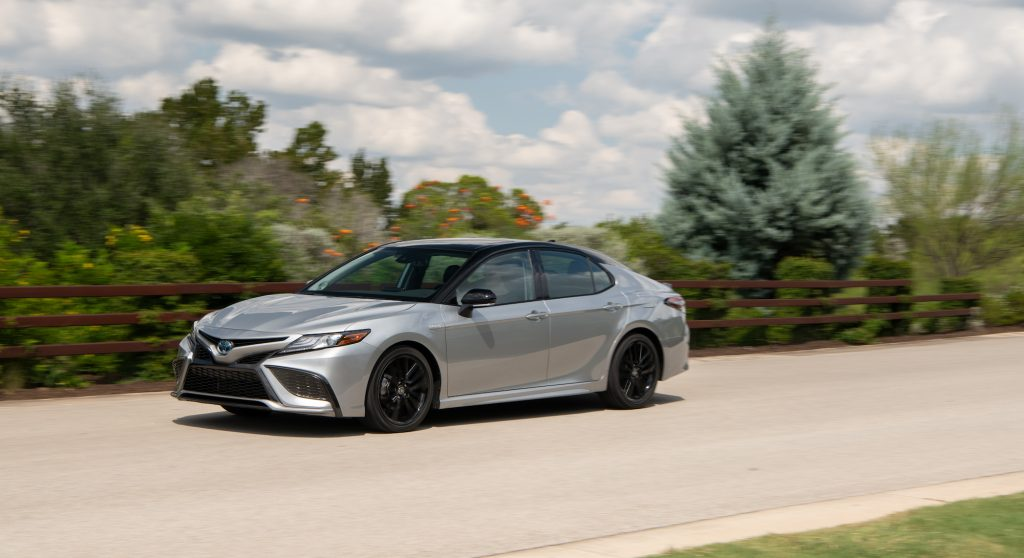 A new silver Toyota Camry XSE Hybrid midsize sedan traveling on a country road along a brown wooden fence and foliage