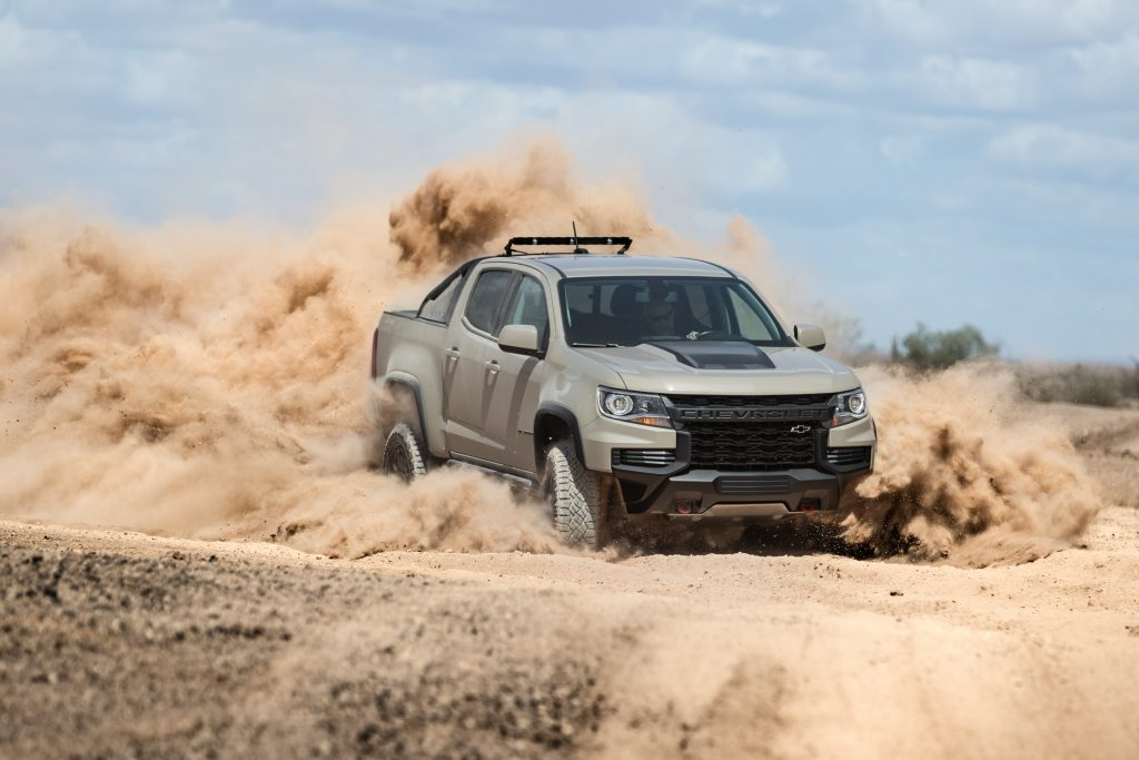A grey and black 2021 Chevy Colorado ZR2 turbo-diesel pickup truck driving off-road, kicking up sand