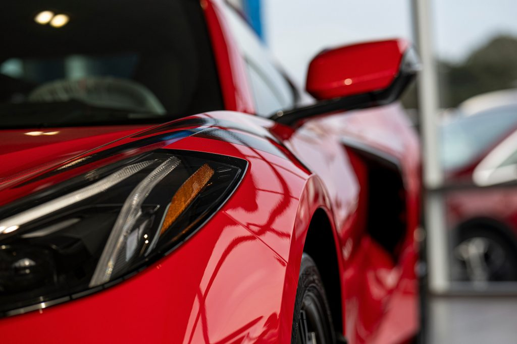 A close-up of a red 2021 Chevy Corvette's driver's-side headlight, side-view mirror, and black side air intake