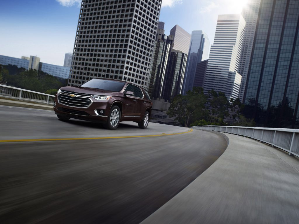 A dark-colored 2021 Chevrolet Traverse three-row midsize SUV traveling on a bridge away from city skyscrapers