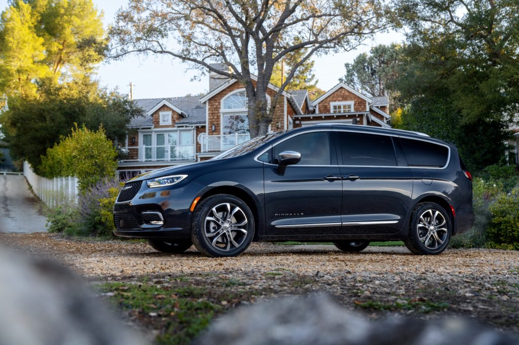 A dark-colored 2021 Chrysler Pacifica Pinnacle minivan parked outside a large shingled home