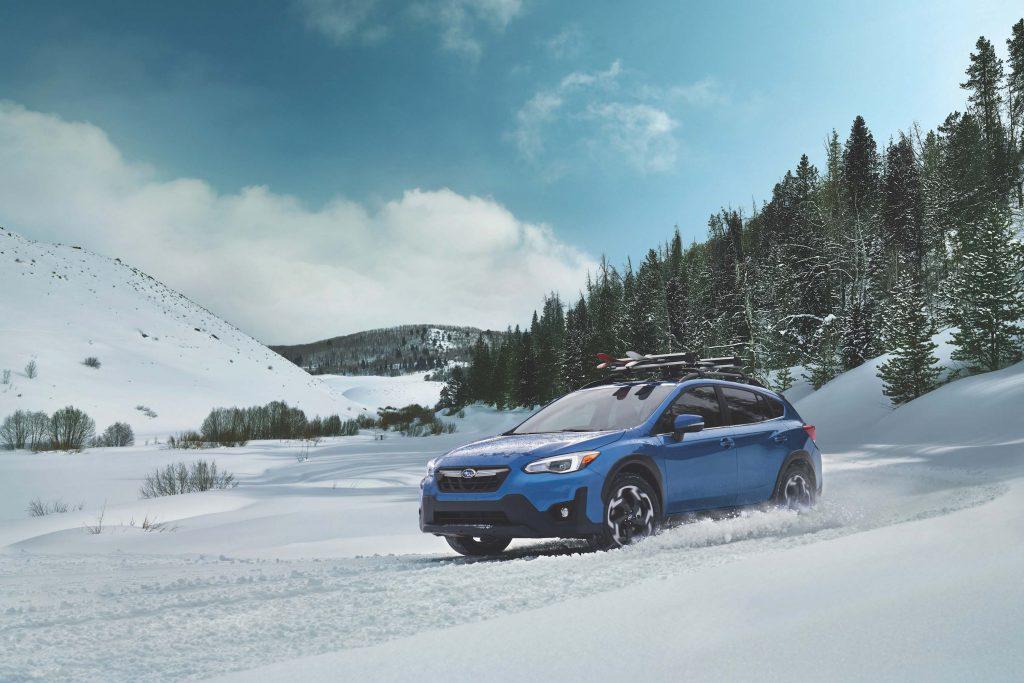 2021 Subaru Crosstrek in blue riding through the snow