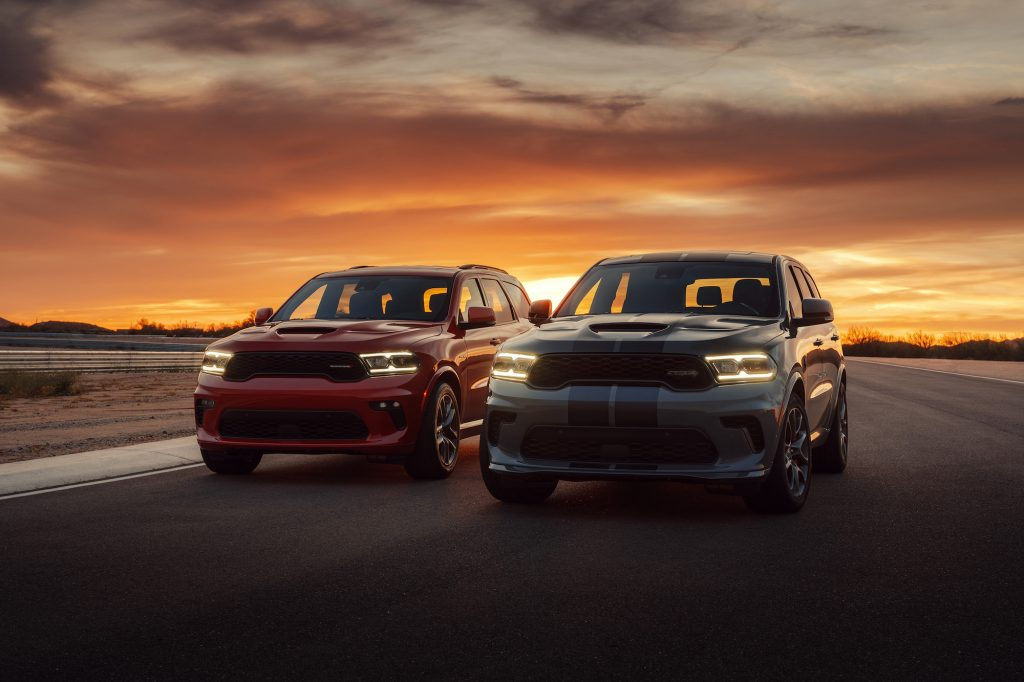 A red 2021 Dodge Durango R/T Tow N Go SUV (left) and a white-and-blue Durango SRT Hellcat SUV parked side-by-side on a racetrack at sunset