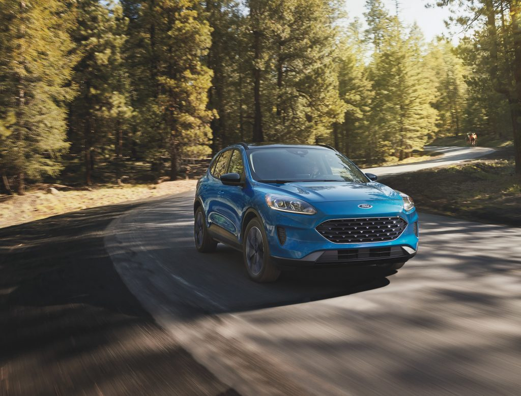 The 2021 Ford Escape in blue driving along a winding road with trees in the background