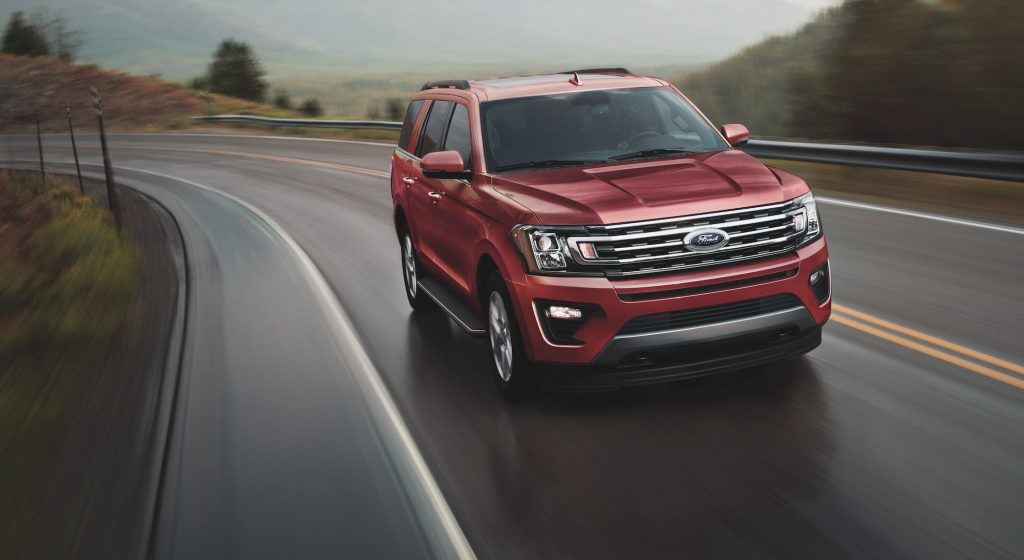 A red 2021 Ford Expedition full-size SUV travels on a two-lane highway up a mountain on a foggy day
