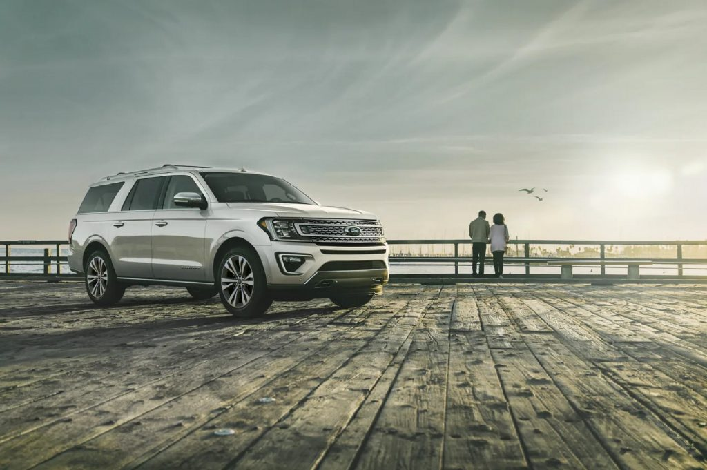 A white 2021 Ford Expedition Platinum on an ocean boardwalk with a couple in the distance