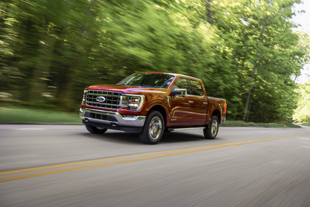 A metallic-red 2021 Ford F-150 Lariat four-door pickup truck traveling on a two-lane highway past thick trees on a sunny day