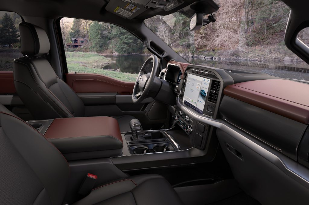 A 2021 Ford F-150 Lariat Sport pickup truck's black-and-maroon interior