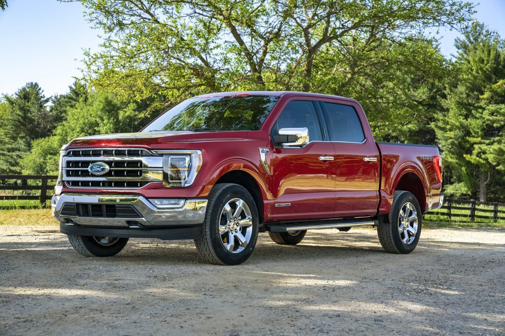 A red 2021 Ford F-150 Turbo-Diesel pickup truck parked on pavement with trees in the background