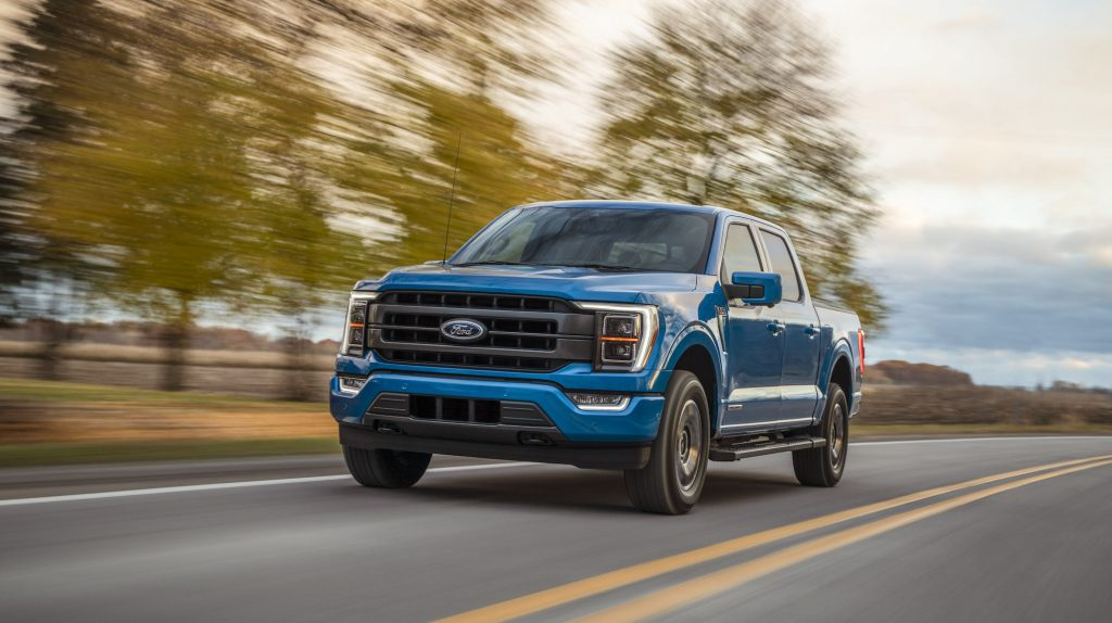 A blue 2021 Ford F-150 Lariat four-door pickup truck traveling on a two-lane highway past fields and trees