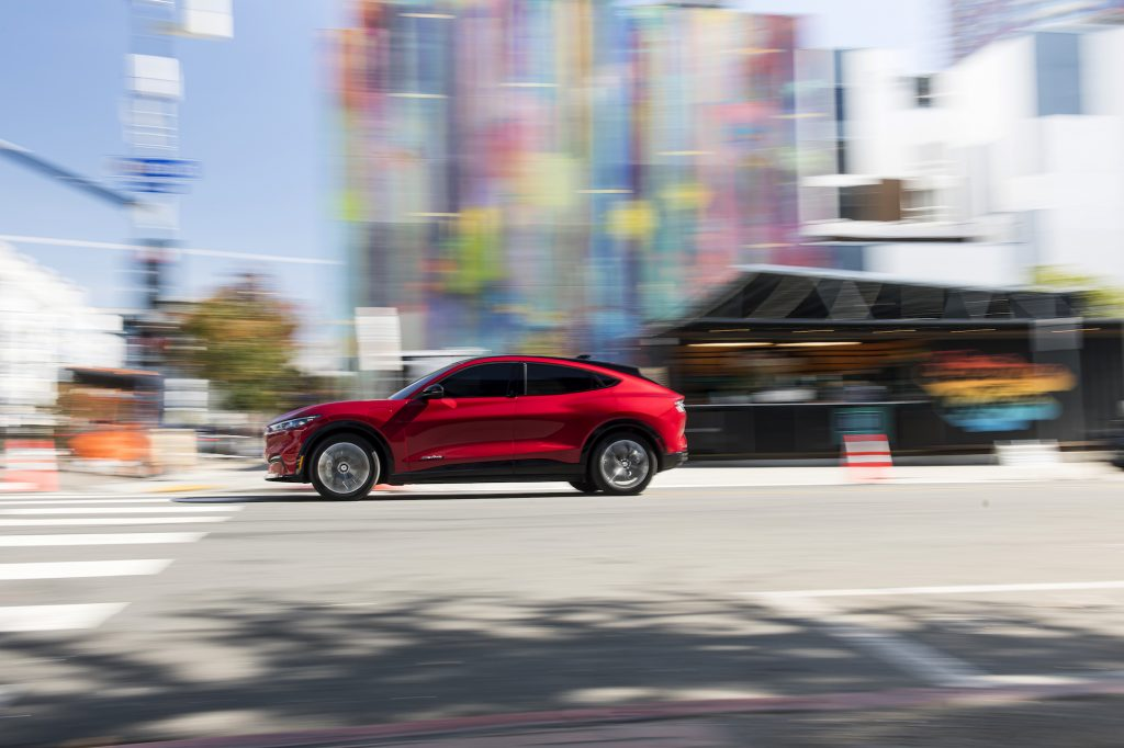 A red 2021 Ford Mustang Mach-E electric crossover SUV approaches a crosswalk at a city intersection on a sunny day