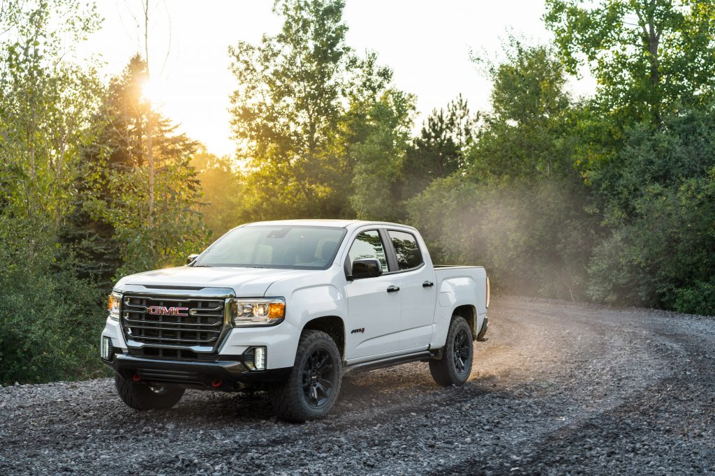 A white 2021 GMC Canyon AT4 Off-Road Performance Edition midsize pickup truck travels on a dusty gravel road through green trees and shrubbery