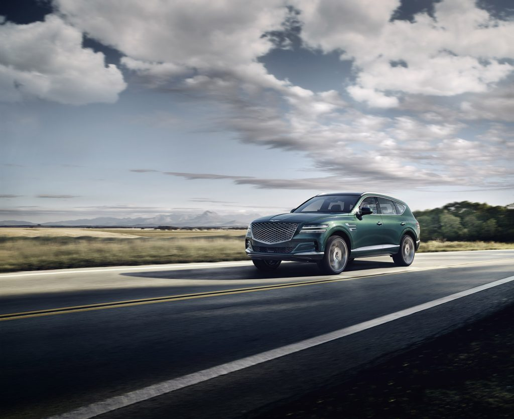 A blue 2021 Genesis GV80 driving down a highway road
