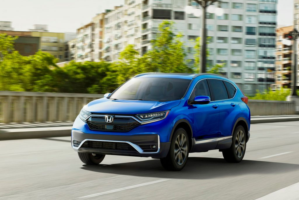 A blue 2021 Honda CR-V Touring driving down a highway road