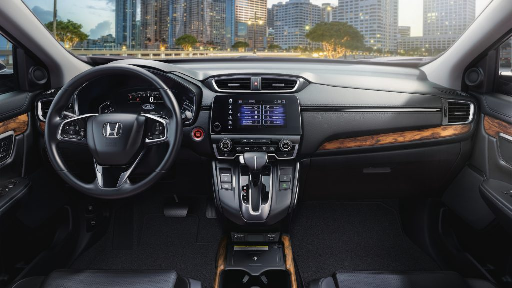 The black and woodgrain-trimmed cockpit of a 2021 Honda CR-V Touring compact crossover SUV