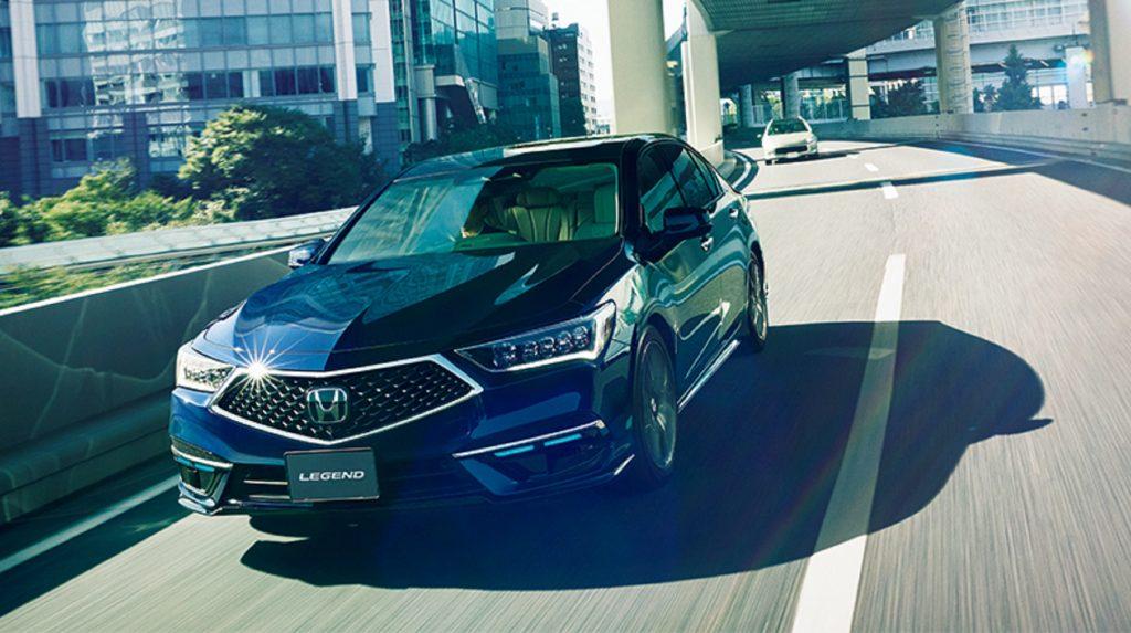 A dark-blue 2021 Honda Legend Hybrid EX with Honda Sensing Elite drives on a Japanese roadway