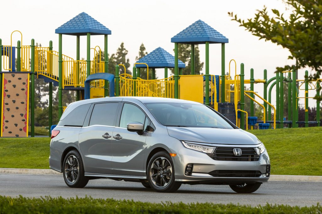 A silver 2021 Honda Odyssey minivan parked outside a colorful playground