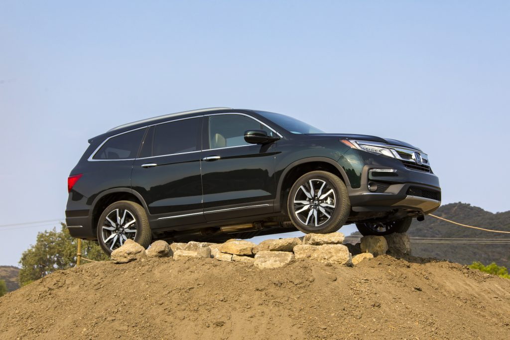 A dark-green metallic 2021 Honda Pilot Elite midsize crossover SUV parked on rocks atop a dirt mound