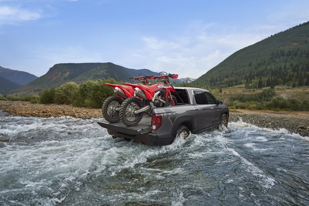 A black 2021 Honda Ridgeline HPD driving through shallow water with two red dirt bikes in the truck bed