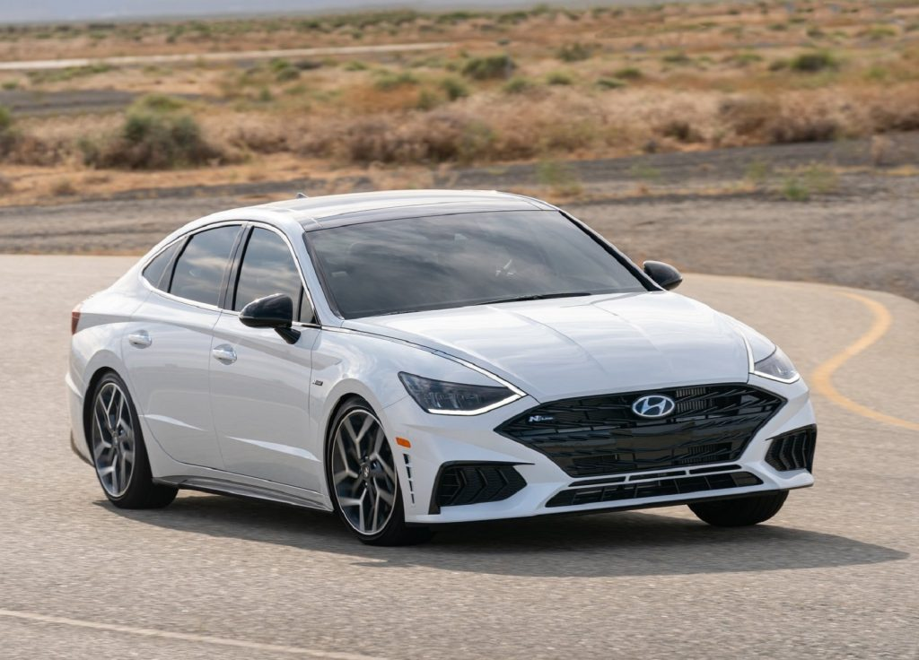 A white 2021 Hyundai Sonata N Line takes a corner on a desert road