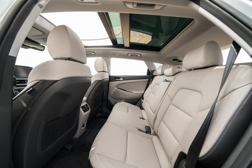 A view of the 2021 Hyundai Tucson compact crossover SUV's white-leather seating and panoramic sunroof