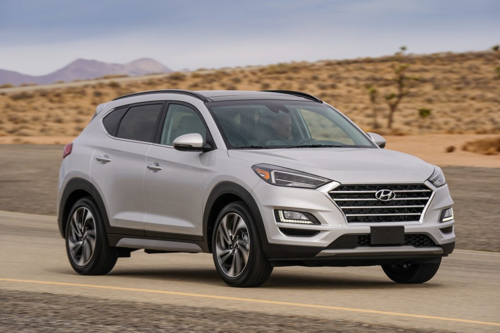 A silver 2021 Hyundai Tucson compact SUV travels on a desert road with mountains in the background