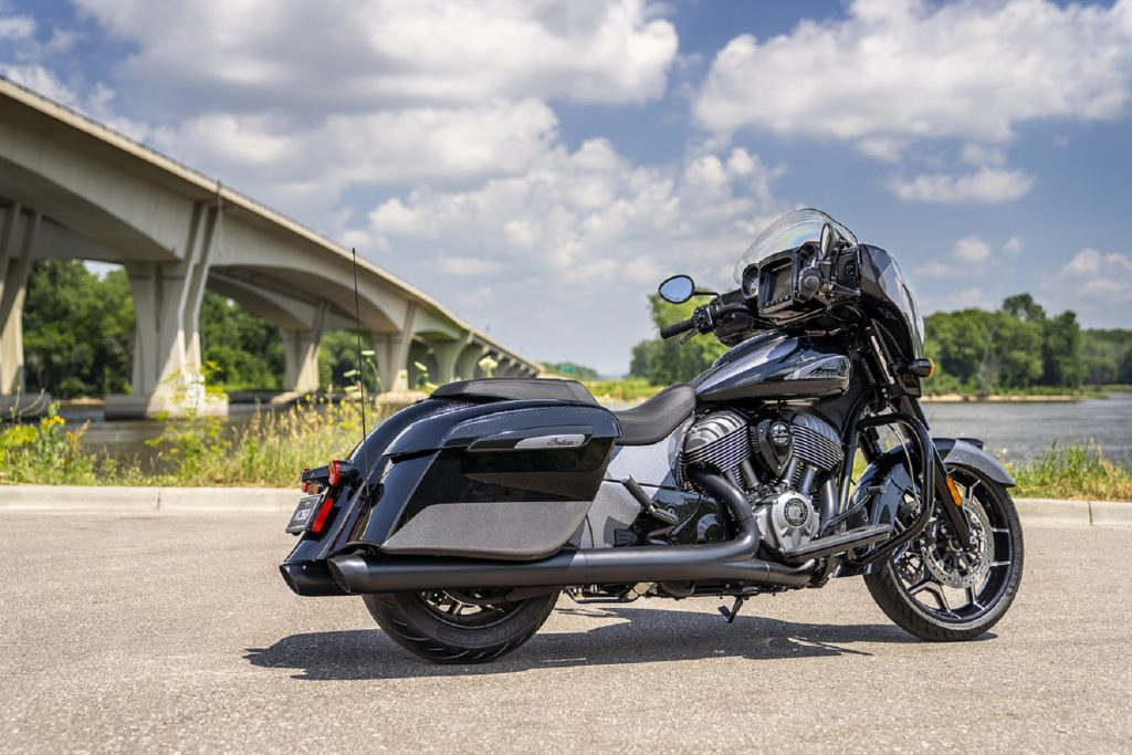 The rear 3/4 view of the metallic-black-and-gray 2021 Indian Chieftain Elite by a riverfront bridge