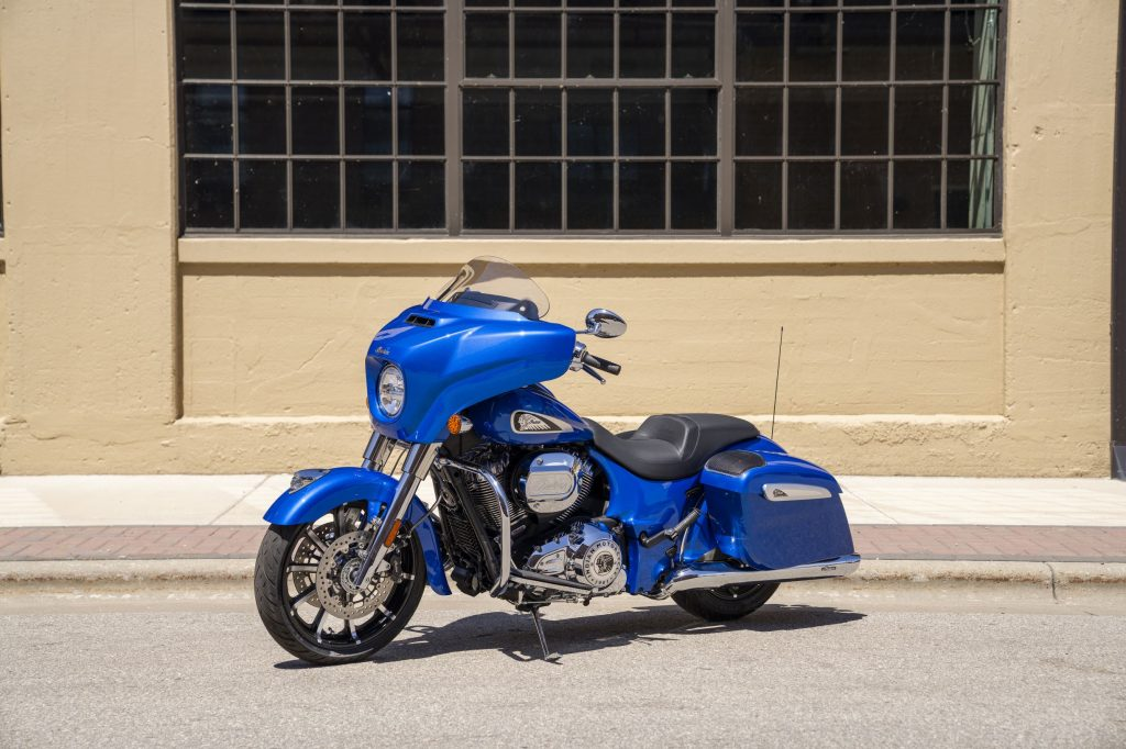 A blue 2021 Indian Chieftain Limited with accessory saddlebag speakers by a tan building