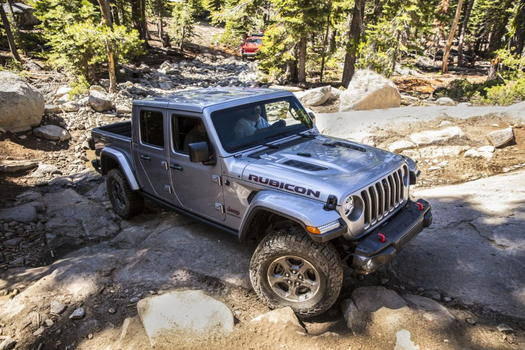A silver 2021 Jeep Gladiator Rubicon climbing up a rocky incline