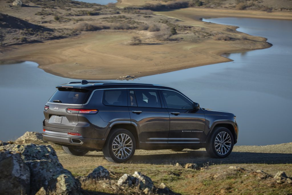 A black 2021 Jeep Grand Cherokee L Summit Reserve parked next to a lake on rugged terrain