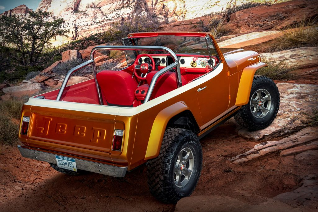 The rear 3/4 view of the orange 2021 Jeep Jeepster Beach concept crawling up a rocky desert trail