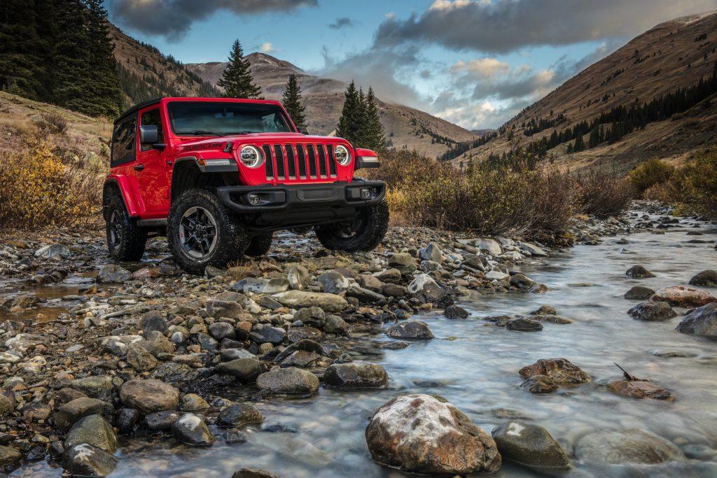 An orange 2021 Jeep Wrangler Rubicon parked on rocky terrain next to a river