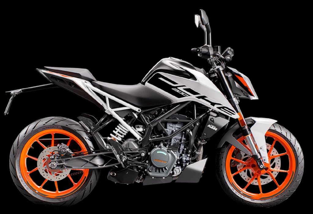 The side view of a white-and-black 2021 KTM 200 Duke with orange wheels