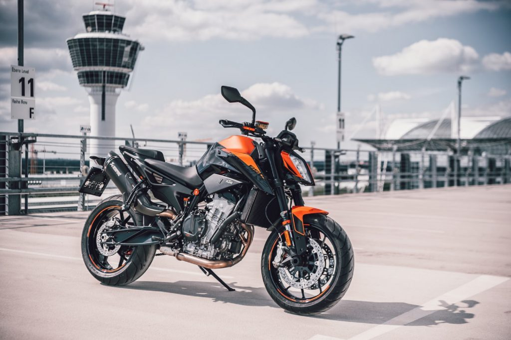 An orange-and-black 2021 KTM 890 Duke with an optional exhaust on an airport bridge