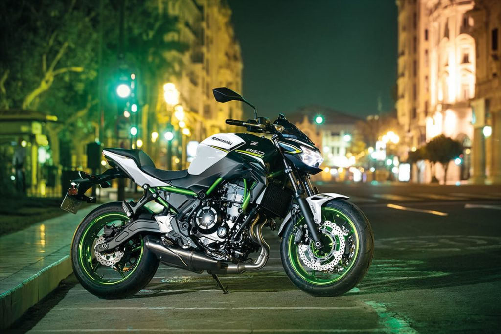A white-black-and-green 2021 Kawasaki Z650 on a well-lit city street at night