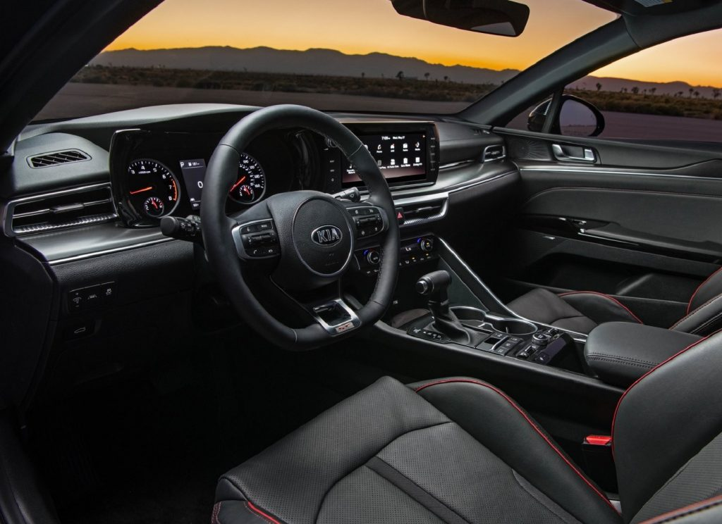 The red-trimmed black front seats and dashboard of the 2021 Kia K5 GT
