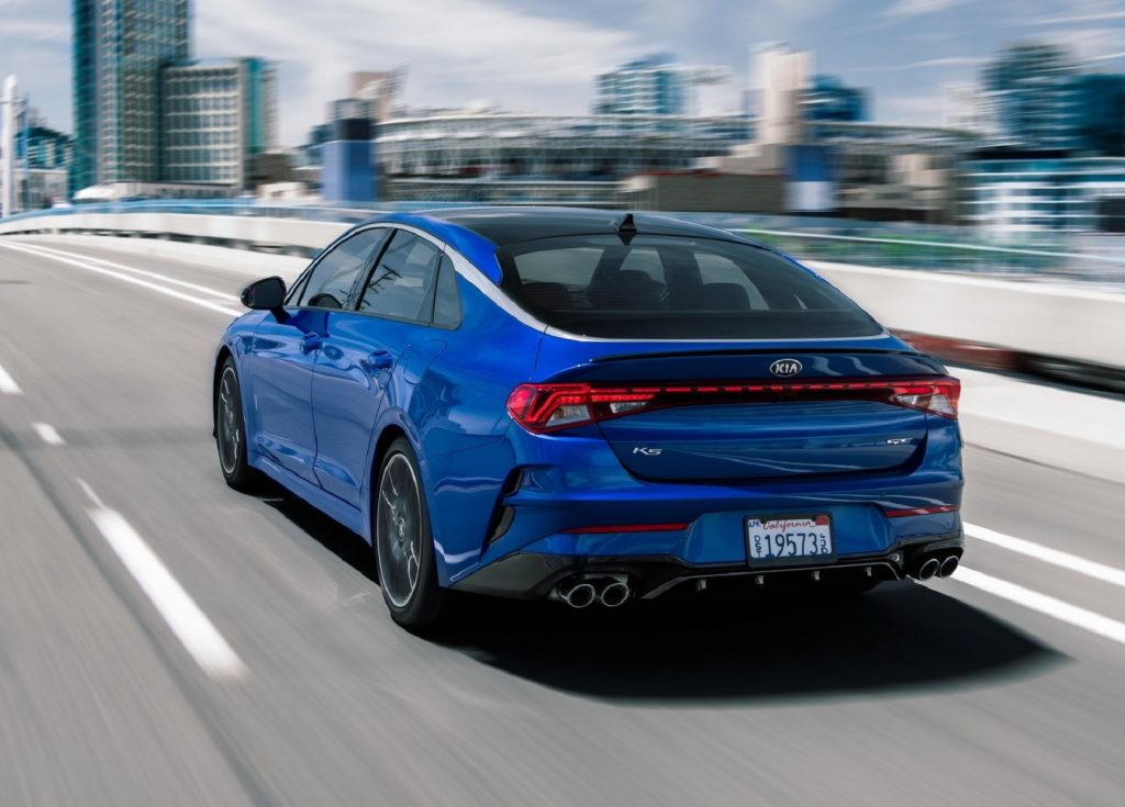The rear 3/4 view of a blue 2021 Kia K5 GT driving over a city bridge