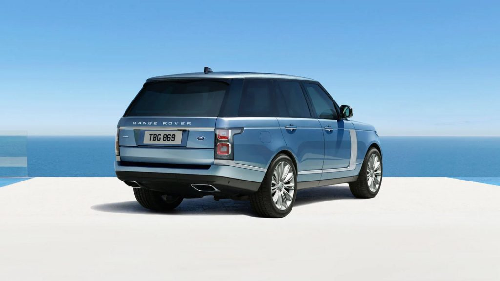 The rear 3/4 view of a blue-and-silver 2021 Land Rover Range Rover Autobiography by the ocean